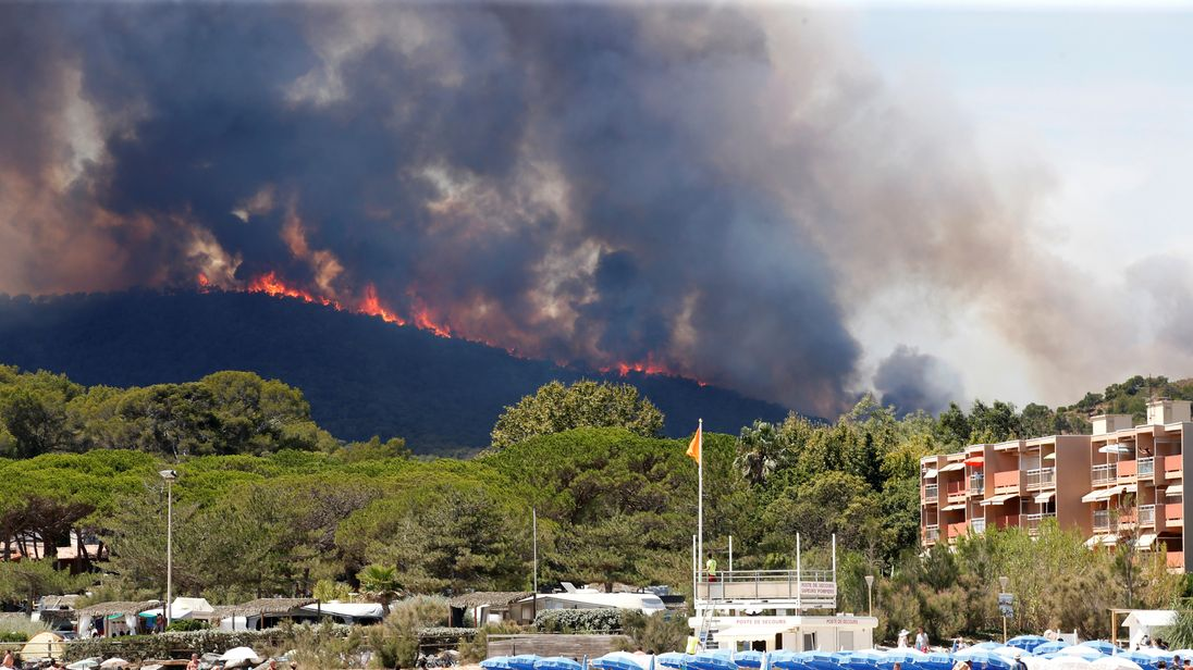 Flames and smoke fill the sky above a burning hillside as tourists swim on the beach in Bormes-les-Mimosas, in the Var department