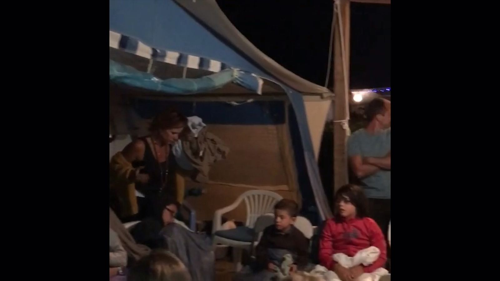 Holidaymakers shelter on the beach after fleeing the forest fires in southern France