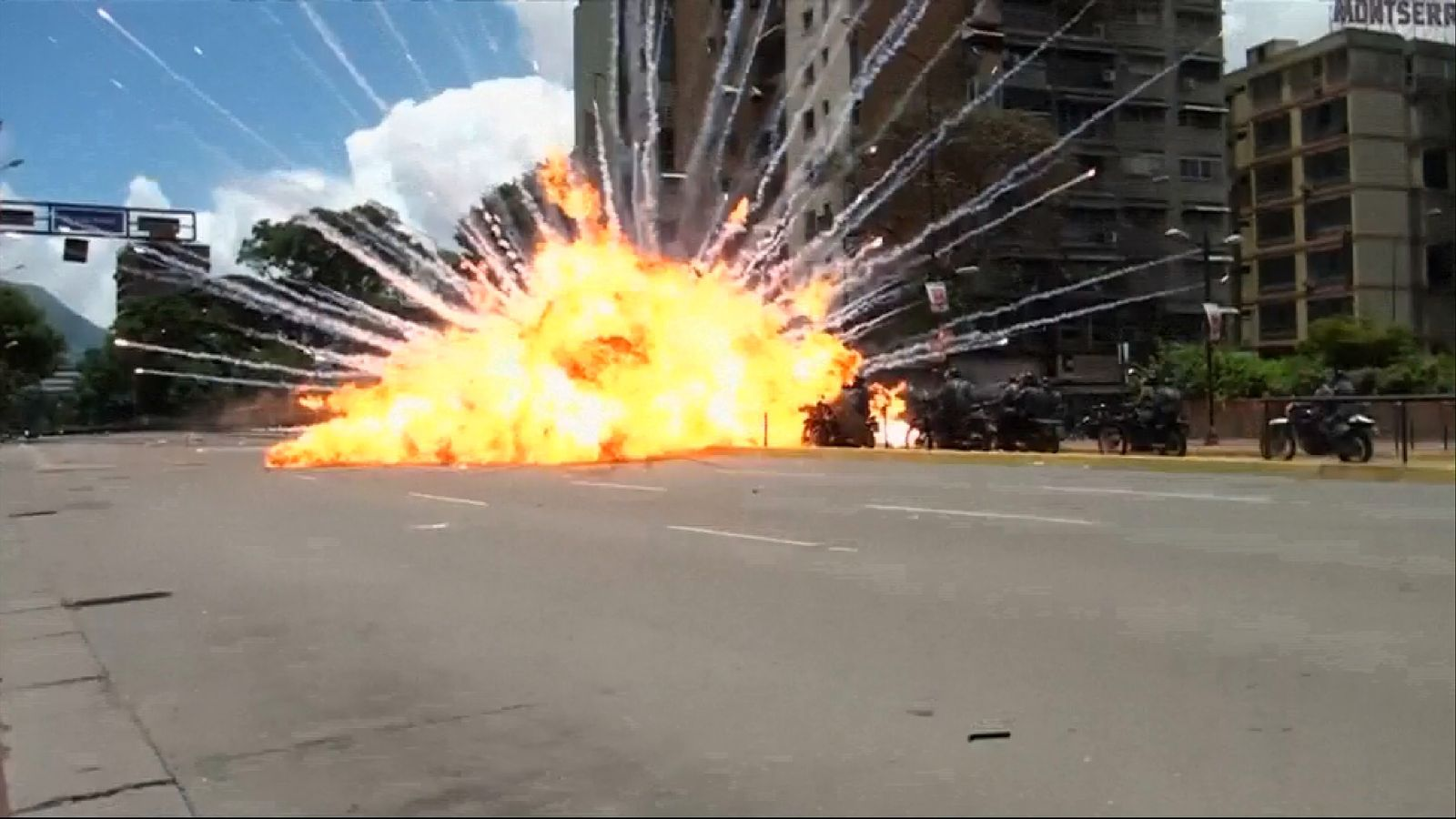 An explosion injures a group of police officers during a protest in Caracas, leaving eight motorbikes smouldering on a main avenue