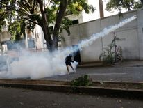 A demonstrator throws back a tear gas canister during clashes