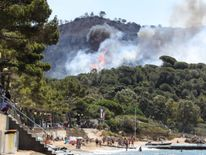 People on the beach as a fire burns a forest by the sea in La Croix-Valmer, near Saint-Tropez