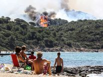People on the beach look at a forest fire in La Croix-Valmer, near Saint-Tropez,