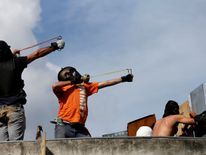 Demonstrators use slingshots during clashes