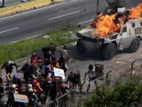 An armored vehicle on fire during clashes with demonstrators