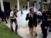 People react as a firecracker explodes outside the National Assembly, in Caracas