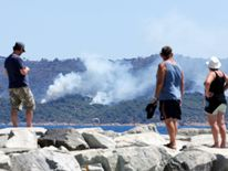 Tourists look smoke that rises from trees at a forest fire on La Croix-Valmer from Cavalaire-sur-Mer, near Saint-Tropez