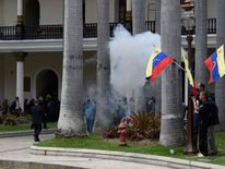 Employees of the National Assembly and members of the press run as Supporters of Venezuelan President Nicolas Maduro storm the building