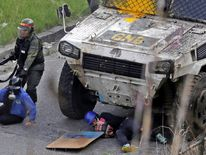 An armoured vehicle hits demonstrators