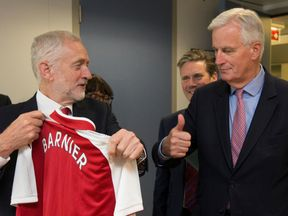 Jeremy Corbyn presents an Arsenal shirt to Michel Barnier during a meeting in Brussels