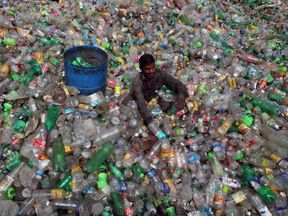 A man sorts bottles at a plastic junkyard in India