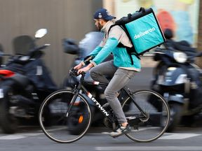 A cyclist rides a bicycle as he delivers a food order for Deliveroo, an example of the emergence of what is known as the 'gig economy'