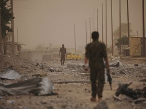 Syrian Democratic Forces (SDF) fighters walk on the rubble of a damaged street in the Raqqa's al-Sanaa industrial neighbourhood, Syria June 14, 2017. Picture taken June 14, 2017. REUTERS/Rodi Said