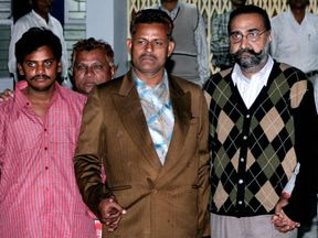 Serial killers Surender Koli (far left) and Moninder Singh Pandher (far right) - policeman centre - are sentenced to death