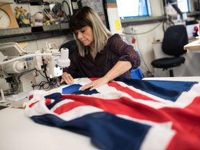 A flag manufacturer stitches and finishes a Union Flag at the factory of 'Flagmakers' in Chesterfield, northern England on March 24, 2017