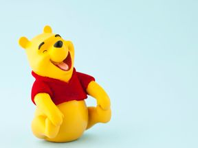 A horizontal studio shot of the Disney character Winnie the Pooh shot on a blue background. Winnie the Pooh was originally created by English author A.A. Milne.