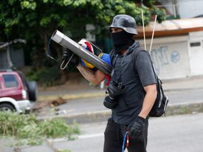 An armed member of the opposition blocks a road as Venezuelans go to the polls