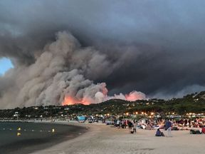 Evacuated people take refuge on the beach and look at a fire burning the forest in Bormes-les-Mimosas, southern France