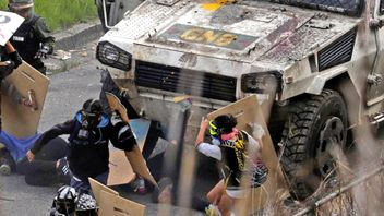 An armored vehicle hits demonstrators during clashes at a rally against Venezuelan President Nicolas Maduro's government in Caracas