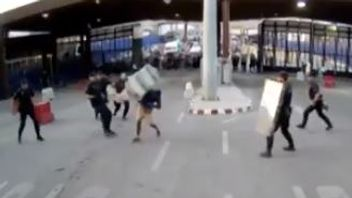 Police throw a plastic barrier at a man at a border checkpoint between Spain and Morocco
