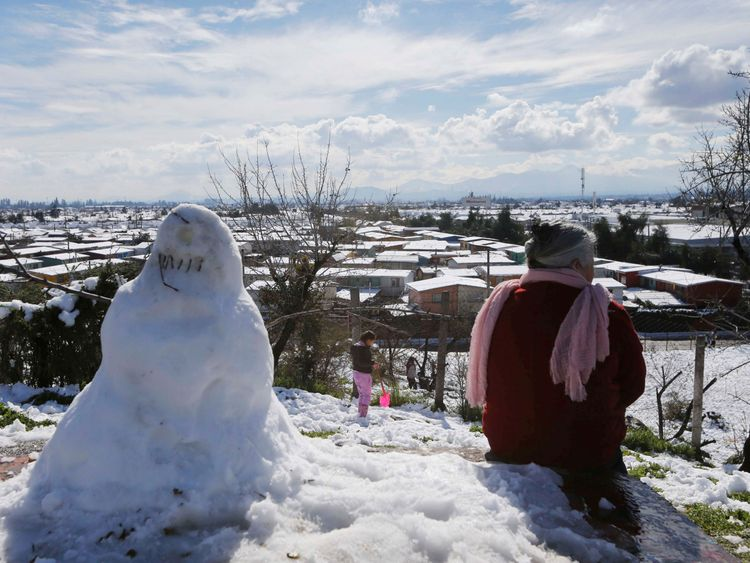 A woman sits near a snowman after an unusual snowfall at Santiago, Chile