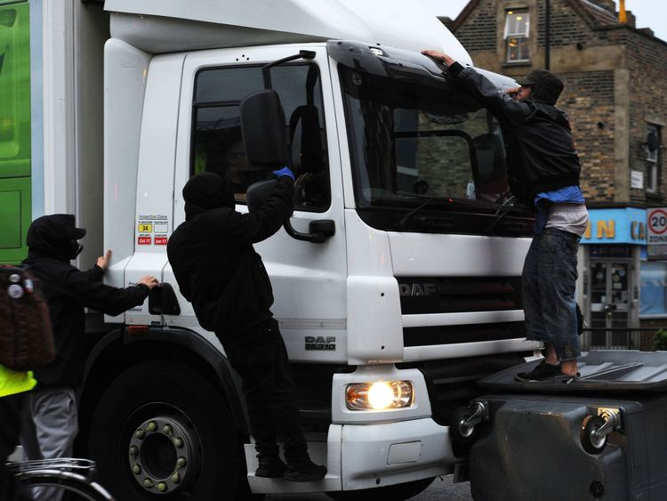 A lorry attempts to drive through makeshift road blocks at a protest in Kingsland Road in east London