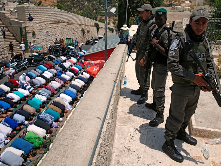 Israeli security forces stand guard as Palestinian Muslim worshippers pray outside Lions Gate, a main entrance to the Al-Aqsa mosque compound in Jerusalem's Old City