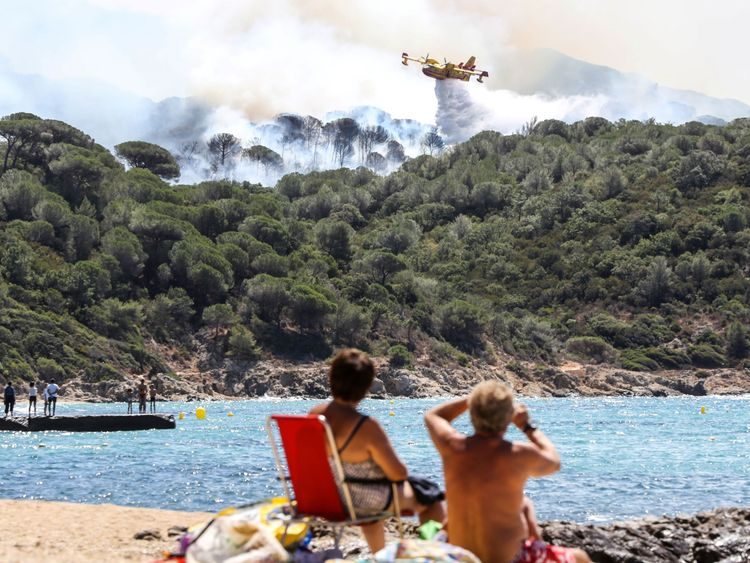 People sit on the beach as they look at Canadair aircraft flying to drop water over a fire in La Croix-Valmer, near Saint-Tropez