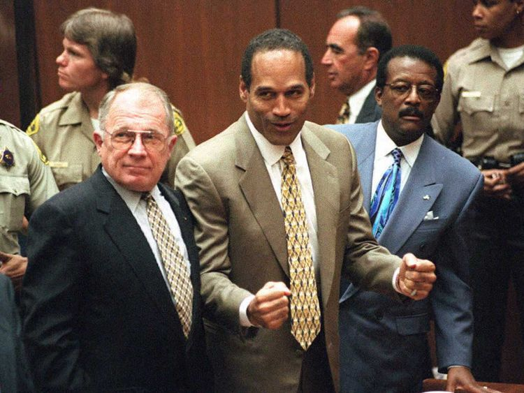 Murder defendant O.J. Simpson listens to the not guilty verdict with his attorneys F. Lee Bailey (L) and Johnnie Cochran Jr (R)