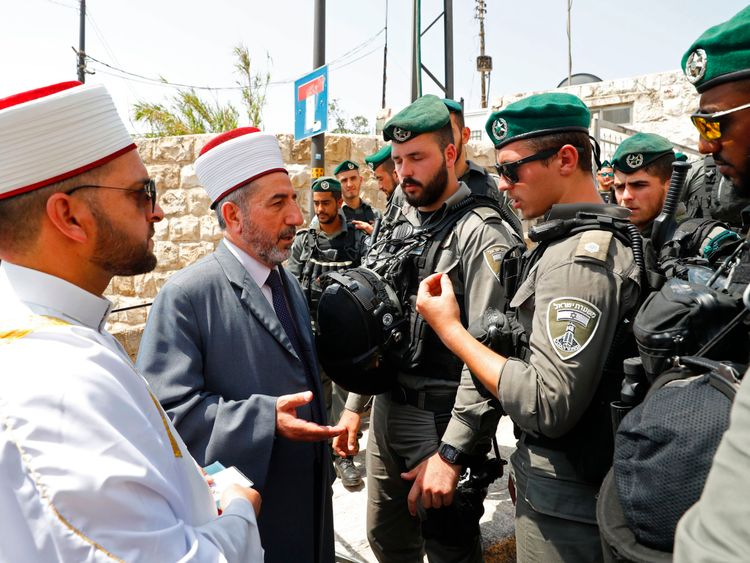 Palestinian Muslim clerics speak with Israeli border guards outside a main entrance to the al Aqsa mosque