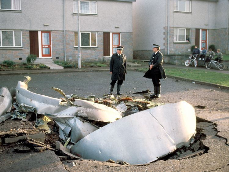 Police officers stand among debris left in the Scottish town of Lockerbie