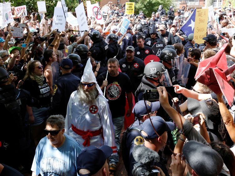Riot police protect members of the Ku Klux Klan from counter-protesters as they arrive to rally in opposition to city proposals to remove or make changes to Confederate monuments in Charlottesville, Virginia