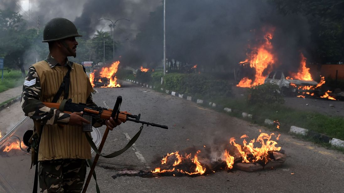Indian security personnel looks at burning vehicles set alight by rioting followers of a religious leader convicted of rape