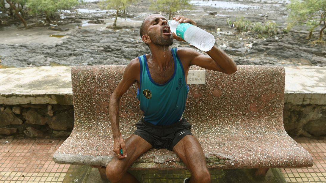Samir Singh drinks water after completing his morning run in Mumbai on 1 August