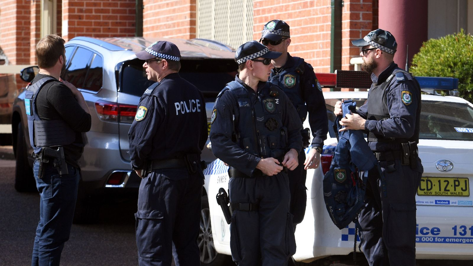 Police emerge from a block of flats in the Sydney suburb of Lakemba on August 1, 2017, after counter-terrorism raids across the city at the weekend