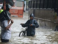 Wading through a flooded street during heavy rain in Mumbai