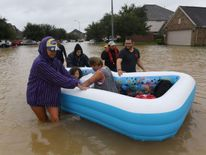 An elderly woman and her granddaughter are evacuated from the Clodine district of Houston