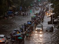 Commuters walk through water-logged roads after rains in Mumbai