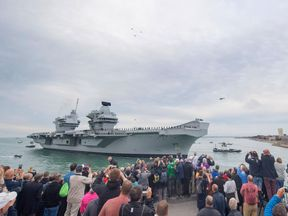 Dozens of spectators lined Portsmouth Harbour to witness HMS Queen Elizabeth's arrival