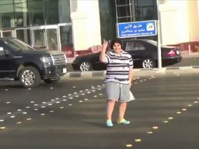 The boy dances in the street with his headphones on