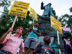 Demonstrators hold signs while standing in front of the statue of Confederate General Albert Pike on August 13, 2017 in Washington, DC, the only member of the Confederate military with an outdoor statue in the US capital, during a vigil in response to the death of a counter-protestor in the August 12 'Unite the Right' in Charlottesville, Virginia
