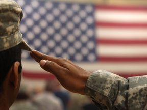 A soldier salutes the flag during a welcome home ceremony for troops arriving from Afghanistan on June 15, 2011 to Fort Carson, Colorado