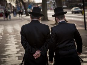 Jewish men walk along the street in the Stamford Hill area on January 17, 2015 in London, England