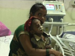 A relative cradles a sick child on a hospital bed at the Baba Raghav Das Medical College