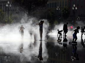 Children play in mist at a water fountain as a heatwave hits south of France in Nice, France August 2, 2017. REUTERS/Eric Gaillard