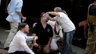 Members of white nationalist protesters receive first-aid during a clash against a group of counter-protesters in Charlottesville, Virginia