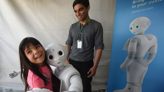 Yaretzi Bernal, 6, gets a hug from 'Pepper' the emotional robot on display during the finals of the DARPA Robotics Challenge at the Fairplex complex in Pomona, California on June 5, 2015