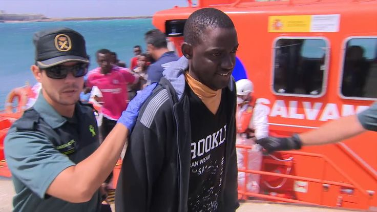 Spanish police lead away a migrant for processing