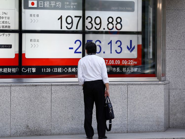 A man looks at an electronic board showing Japan's Nikkei average outside a brokerage at a business district in Tokyo, Japan August 9, 2017. REUTERS/Kim Kyung-Hoon