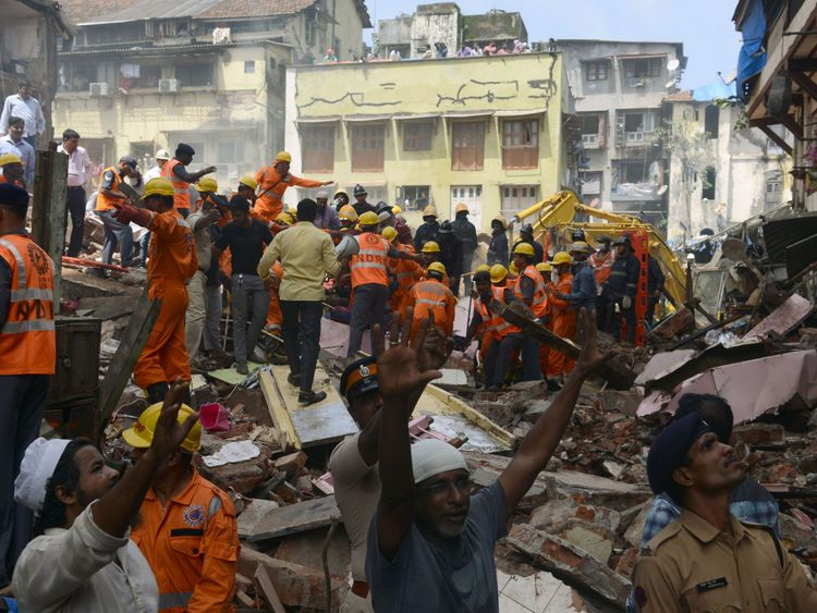 Rescue workers and residents look for survivors at the site of a building collapse in Mumbai