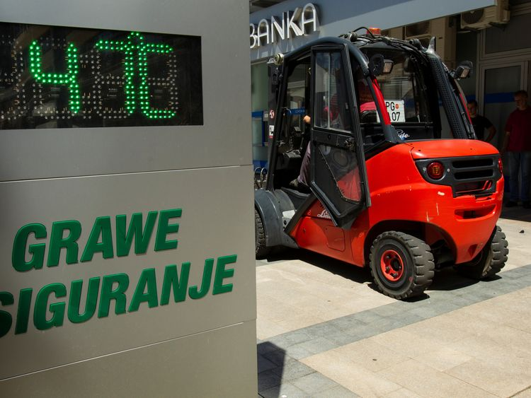 A worker operates a forklift next to a street thermometer showing 47 degrees Celsius in Podgorica, Montenegro, August 4, 2017